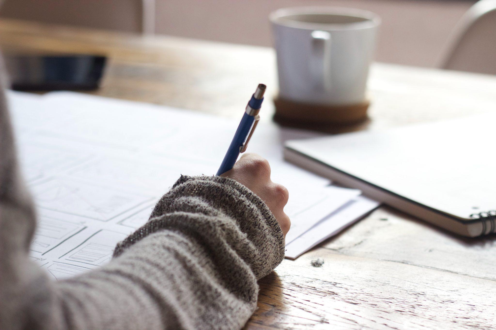Femme qui écrit avec tasse