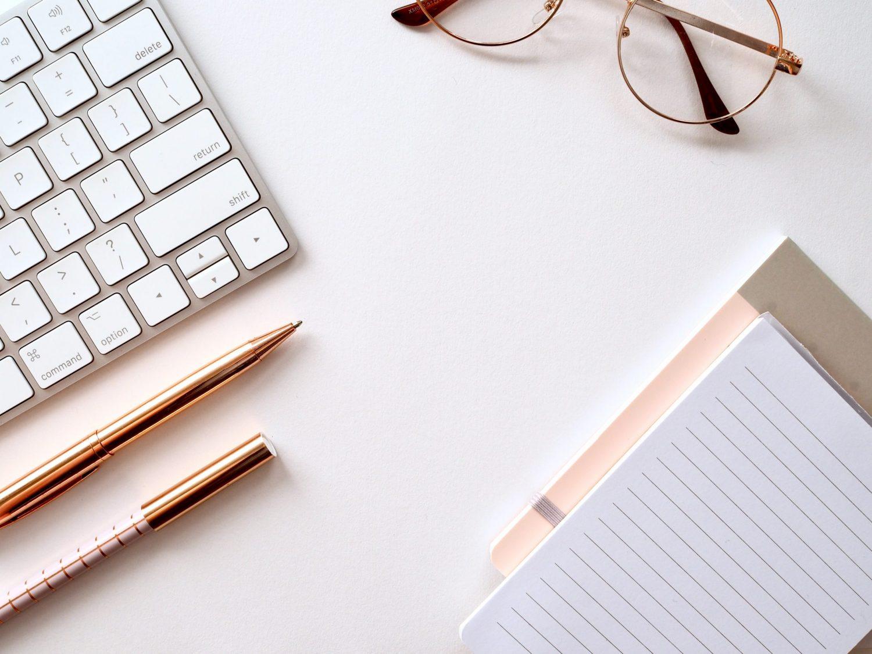 Vue aérienne d'un ensemble de clavier, lunettes, crayons et carnets